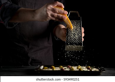 Cooking focaccia bread or pizza by chef hand with olives, oil, parmesan and herbs rosemary. Recipe home cooking from chef. Dark background with space area  for text or design. Horizontal photo.
