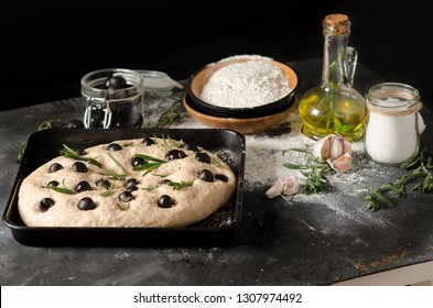 Cooking focaccia bread. Raw focaccia with ingredients on the table, olives, rosemary.