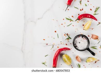 Arrière-plan cuisine, table en marbre Blanc avec épices - poivre rouge chaud, assaisonnements, ail, sel, verts, estragon, persil, herbes, citron vert, espace pour copie de vue de dessus