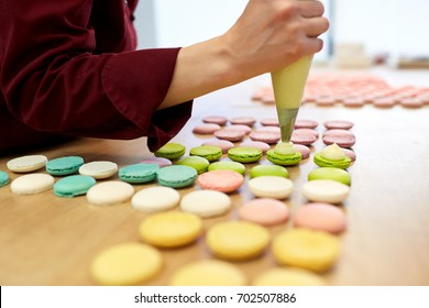 cooking, food and baking concept - chef with confectionery bag squeezing cream filling to macarons shells at pastry shop