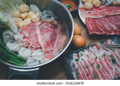 Cooking food by put a flesh beef, pork, egg and vegetable in to a hot pot for make a sukiyaki or shabu at japanese shabu buffet restaurant