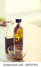 cooking and food concept - close up of two olive oil bottles and bowl of oil