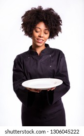 cooking and food concept - smiling African female chef, cook or baker with empty plate