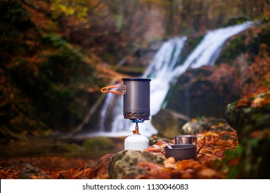 Cooking food in nature. Tourist tableware. The gas burner heats the water in the bowler. Outdoor mug, bowl, spoon nearby. Autumn leaves, mountain forest, picturesque waterfall on a blurred background.