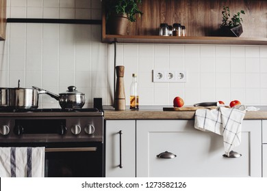 Cooking food on modern kitchen with steel oven, pots, knife on wooden cutting board with vegetables, pepper, spices,oil on wooden tabletop. Home food. Stylish kitchen furniture in grey color