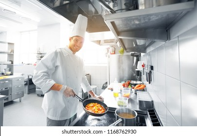 cooking food, profession and people concept - happy male chef cook with pot and frying pan at restaurant kitchen