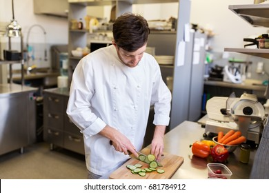 cooking food, profession and people concept - happy male chef cook with knife chopping cucumber on cutting board at restaurant kitchen
