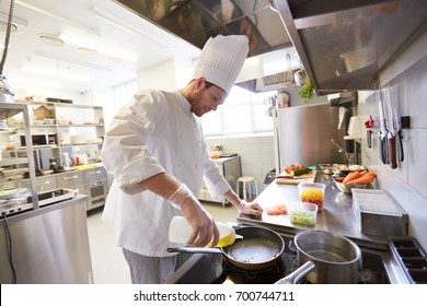 cooking food, profession and people concept - happy male chef cook pouring oil to frying pan at restaurant kitchen