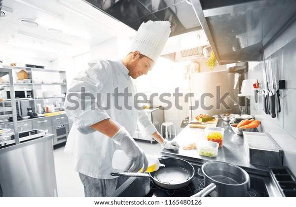 cuisine, profession et concept de personnes - chef masculin heureux cuisinier cuisinier mâle qui verse de l'huile à la poêle à la cuisine du restaurant