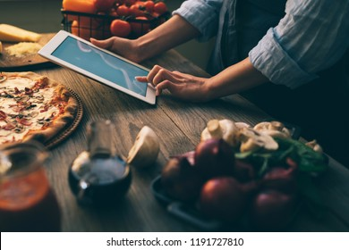 Cooking, food, technology and people concept. Young woman using a tablet computer to cook pizza in her kitchen. A woman searching the cooking pecipe and preparing food ingredient before cooking.