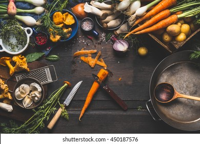 Cooking with forest mushrooms and  vegetables ingredients and kitchen tools, preparation on dark rustic wooden table, top view