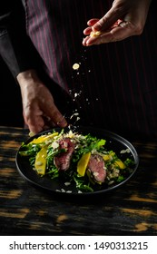 Cooking fresh diet keto salad with beef meat, arugula, fruits and nuts by chef hands on black table background.