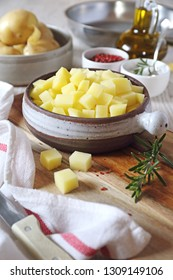 Cooking of fried potatoes. Kitchen-ware, crude potato cut in small cubes and olive oil