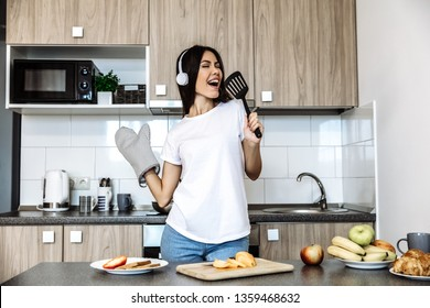 Cooking  and fun. At home. Asian girl listen music in headphones and singing in the kitchen