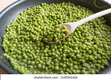 cooking green peas in black frying pan with wooden spoon, stewed vegetables with onion and others herbs