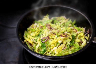 cooking green savoy cabbage with red onions in a black pan on a stove, healthy winter vegetable, selected focus, narrow depth of field