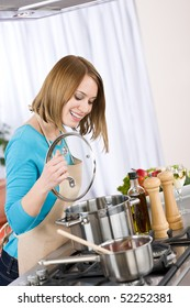 Cooking - Happy woman by stove in kitchen with pots and pans
