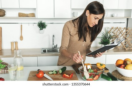 Cooking healthy food in home kitchen concept. Beautiful young woman preparing summer salad