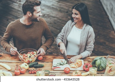 Cooking healthy. Top view of beautiful young couple preparing healthy salad together and smiling