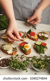 Cooking healthy vegetarian sandwiches. Female hands decorating assorted whole grain vegetable bruschettas with spices and microgreen. Eating right concept, food background