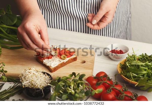 Cooking healthy vegetarian sandwiches. Female hands making whole grain bruschetta with avocado topping, juicy cherry tomatoes and microgreen. Eating right concept