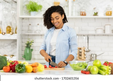 Cooking At Home. Beautiful young black woman preparing vegetable salad in modern kitchen, cutting tomatoes, copyspace