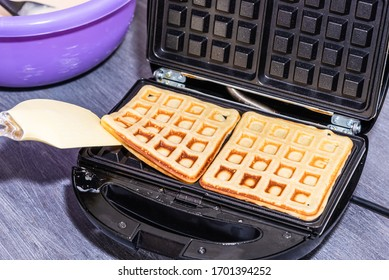 Cooking home Belgian waffles in an electric waffle iron.