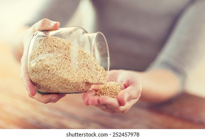 cooking and home concept - close up of female emptying jar with quinoa