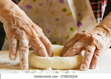 Cooking at home, old woman's hands kneading dough, getting the bread ready to be baked