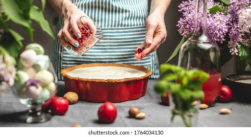 Cooking homemade cranberry pie. A female pastry chef is sprinkling cranberry berries on lingonberry tart with white sour cream. Table with bright ingredients in spring style with flowers