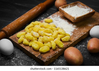 Cooking Homemade Potato dumplings Gnocchi on wooden board. On black wooden table background ingredients for Potato dumplings Gnocchi raw potatoes, flour, chicken eggs.