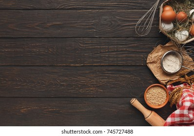 Cooking ingredients background. Border of flour and wheat grains in bowls, eggs and whisk on dark rustic wood with copy space. Dough preparing and pastry concept, top view