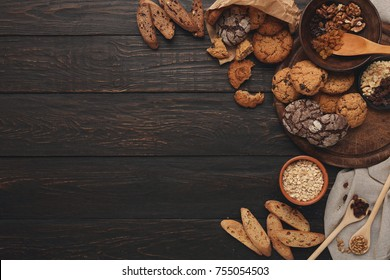 Cooking ingredients for homemade oatmeal cookies and biscotti. Oat flakes and flour in wooden bowls at dark rustic background with copy space, top view. Handmade pasty concept and recipe mockup