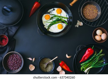 Cooking ingredients in the process of cooking the fried eggs,  view from above, culinary background with a space for a text