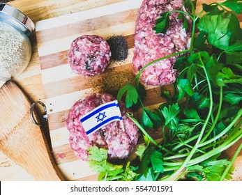 Cooking of israeli cutlets and kebabs with a fresh green parsley, spices and wooden utensils on a wooden background. Making kosher kebabs with a mincemeat wallpaper. Recipe of tasty kosher cutlets.
