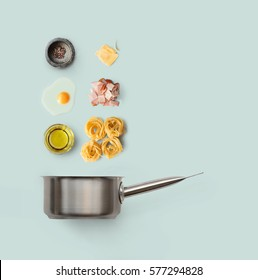 Cooking italian food collage. Ingredients for carbonara pasta, spaghetti, oil, ham, egg and parmesan isolated on blue background with saucepan.
