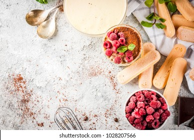 Cooking Italian food dessert Tiramisu, with all the necessary ingredients cocoa, coffee, mascarpone cheese, mint and raspberries, on grey stone background.  Copy space top view