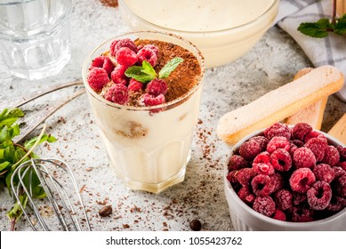 Cooking Italian food dessert Tiramisu, with all the necessary ingredients cocoa, coffee, mascarpone cheese, mint and raspberries, on grey stone background.  Copy space