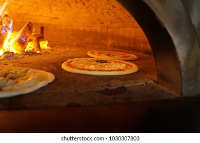 cooking Italian pizza in a wood oven