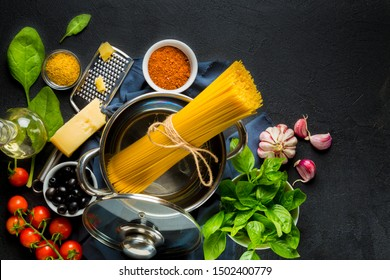 Cooking Italian Spaghetti Pasta. Raw materials for cooking on a black background