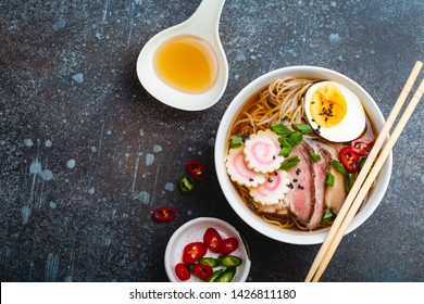 Cooking Japanese noodle soup ramen. Ramen with sliced pork, narutomaki, egg, kitchen spoon with broth on rustic stone background. Making traditional dish of Japan, top view, close-up. Space for text