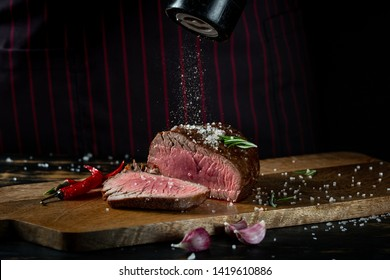 Cooking juicy beef steak by chef hands on dark black background with copy space for text menu or recipe.