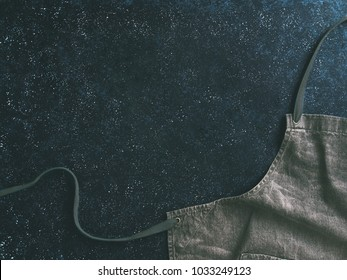 Cooking and kitchen background - trendy denim cotton apron on dark background with copy space. Gray kitchen apron on dark table as kitchen background with space for text. Top view or flat-lay.