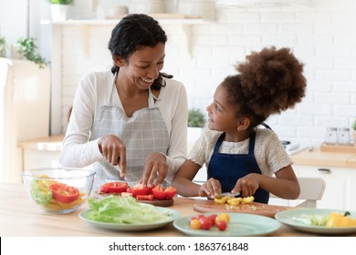 Cooking lesson. Happy patient black foster mom teaching little adopted daughter prepare healthy nutrition, single african mommy and preteen girl talking smiling engaged in useful activity at kitchen