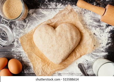 Cooking with love. Dough in heart shape top view. Baking ingredients on the dark wooden table