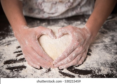 Cooking with love. Female hands holding dough in heart shape