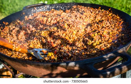 Cooking and making traditional Spanish Paella in iron cast pan. Preparing big paella outdoors on front yard party or business event. Professional catering buffet food.