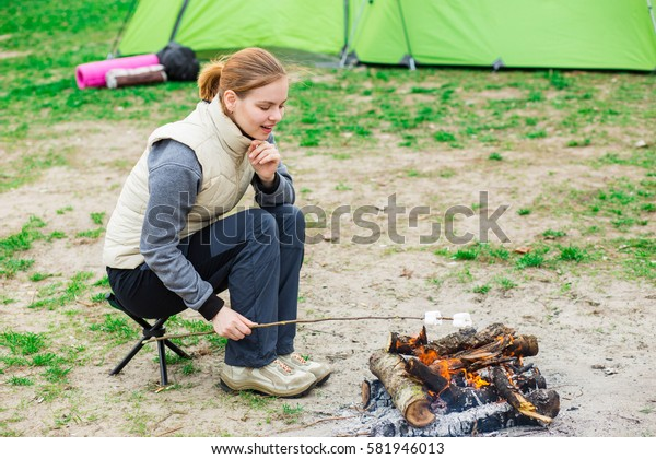 Cooking marshmallows on fire during the holiday camping. Positive woman in trekking clothes sitting on a folding chair beside a campfire and roasts marshmallows