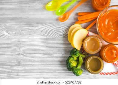 cooking mashed carrots for baby on wooden background top view