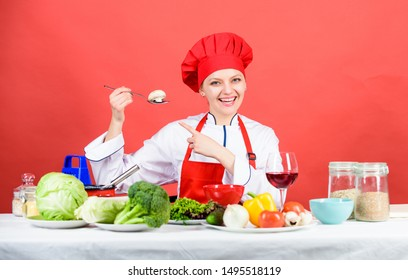 Cooking meal. Professional cooking tips. Woman chef try taste eat food. Delicious recipe concept. Girl at kitchen table. Cooking food and housekeeping. Housewife routine. Cooking healthy food.